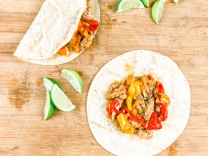 A cutting board with two chicken fajitas - one open and one closed.