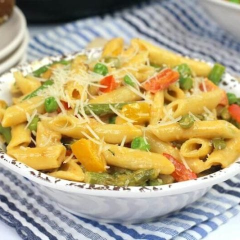 A white bowl filled with chicken pasta with asparagus and peas.