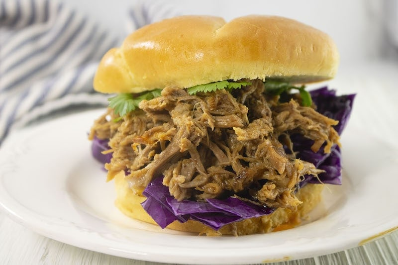 A pulled pork sandwich piled high with red cabbage and lettuce.