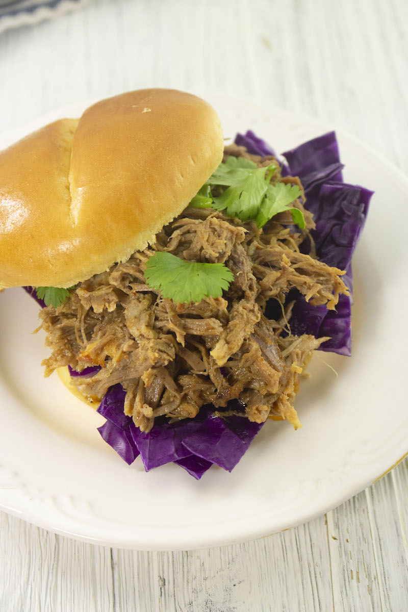 A pulled pork sandwich with top bun sliding off to the side.