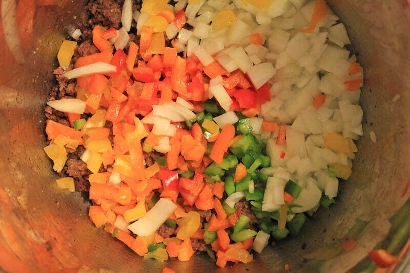 Peppers, tomatoes, and onions inside instant pot.