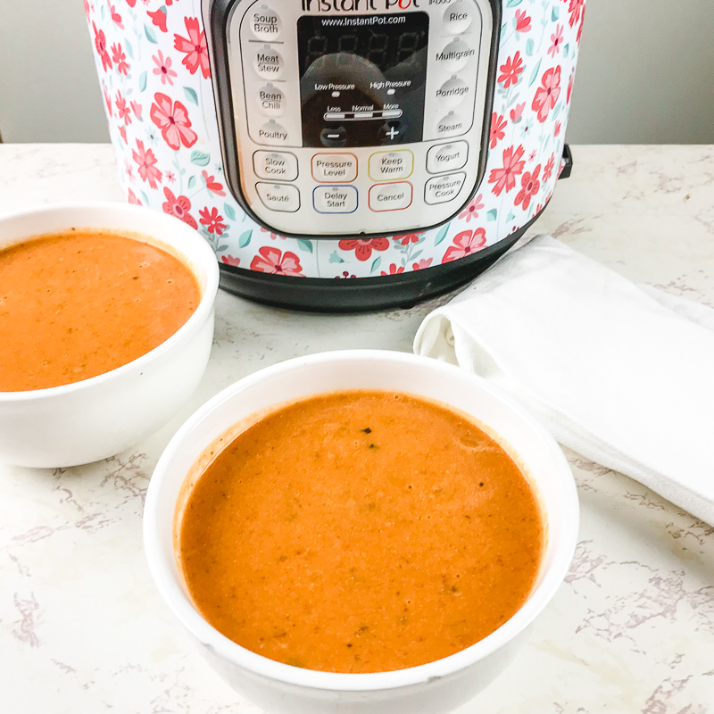 A bowl of tomato soup in front of an instant pot with floral print.