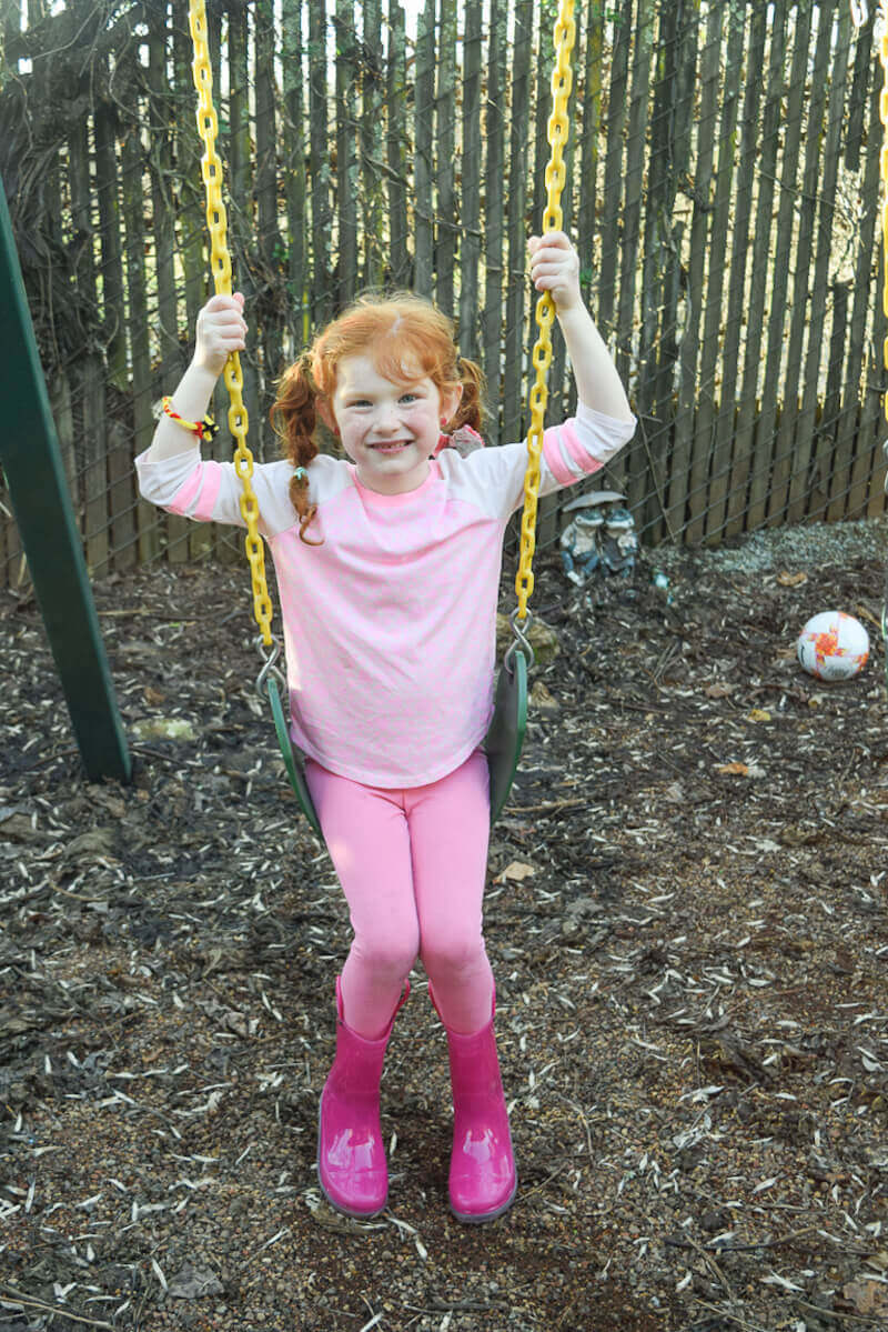 Girl in pink sitting on swing.