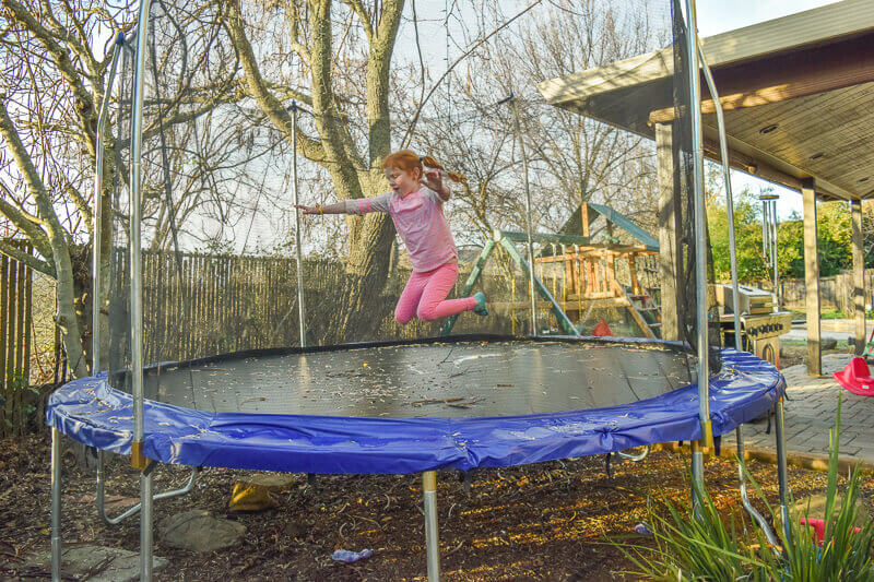 Little girl in pink jumping on large trampoline.