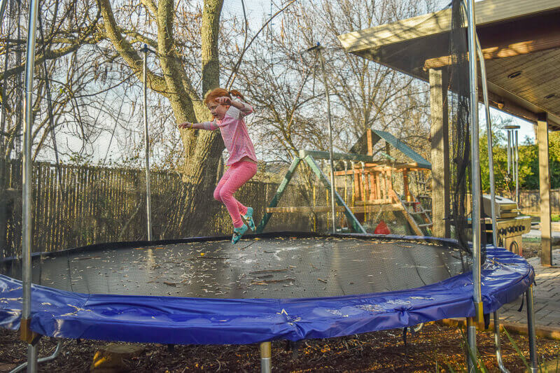 Girl in pink jumping on trampoline.
