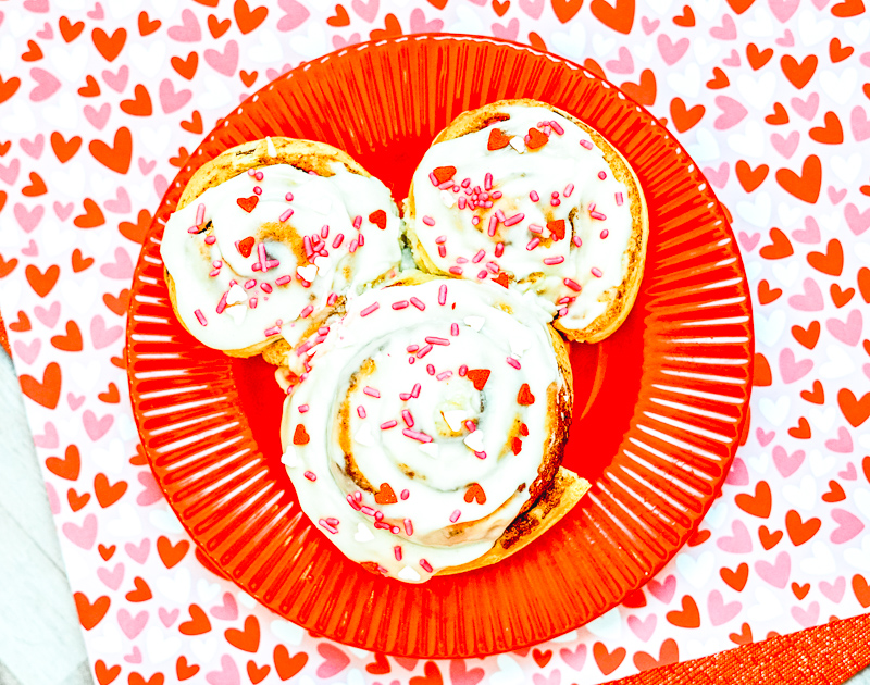 A red plate with a Mickey shaped cinnamon roll