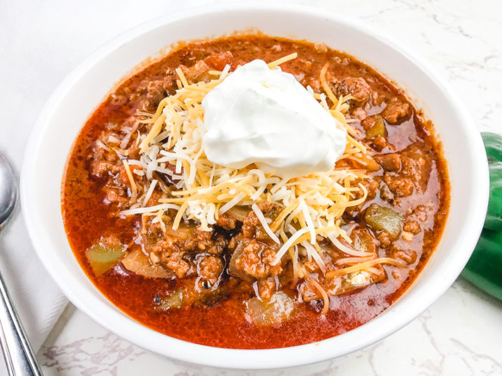 Close up of no bean chili topped with sour cream.