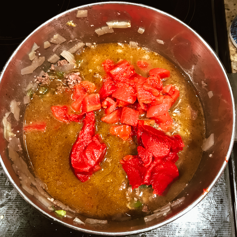 Tomatoes and spices added into pot of cooked beef and peppers.