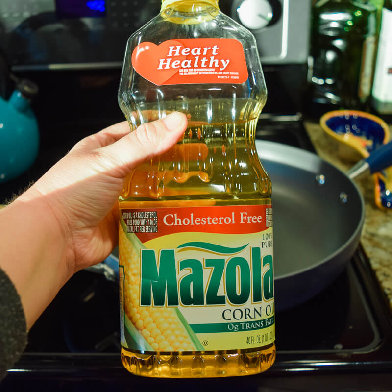 A bottle of corn oil being held in front of hot skillet.