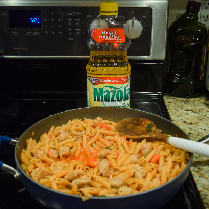Pasta fully cooked inside of skillet next to bottle of Mazola Corn Oil.