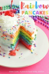 Close up of a stack of colored pancakes with colorful beads in the background.