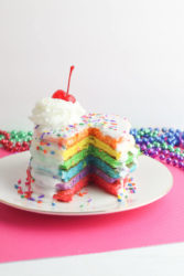 A tall stack of colorful rainbow pancakes with frosting and sprinkles.
