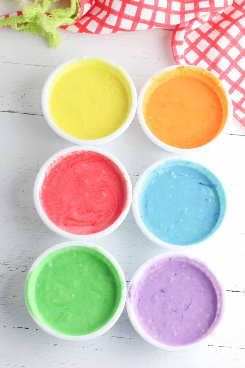 6 bowls of pancake batter, each dyed a different color.