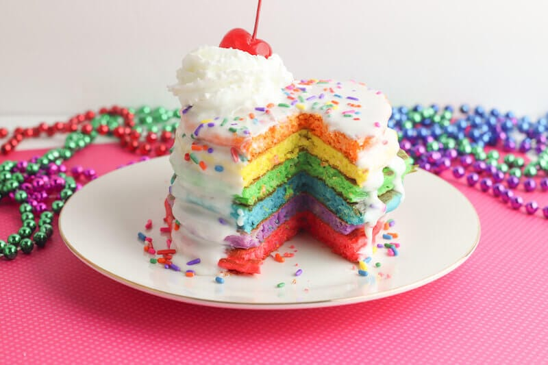 A stack of rainbow colored pancakes with a triangle cut out of them, showing the colors.
