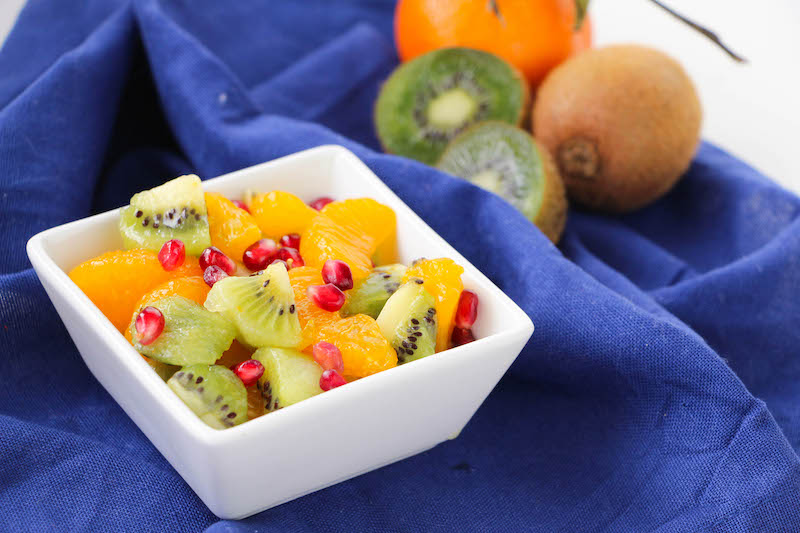 Square dish with fruit salad and a kiwi and clementines in the background.