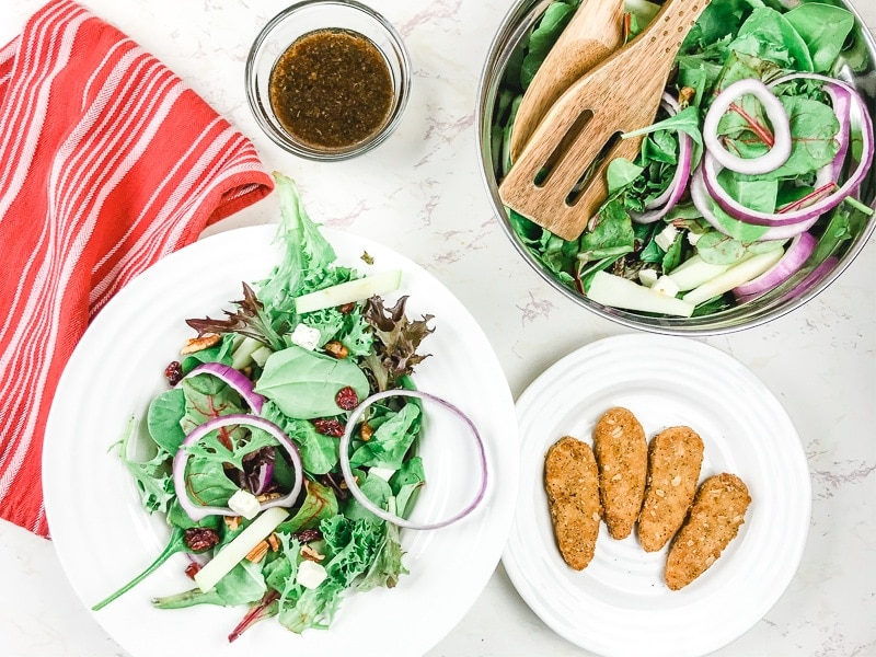 A white bowl of winter salad next to a metal bowl of salad and a white plate of crispy tenders.