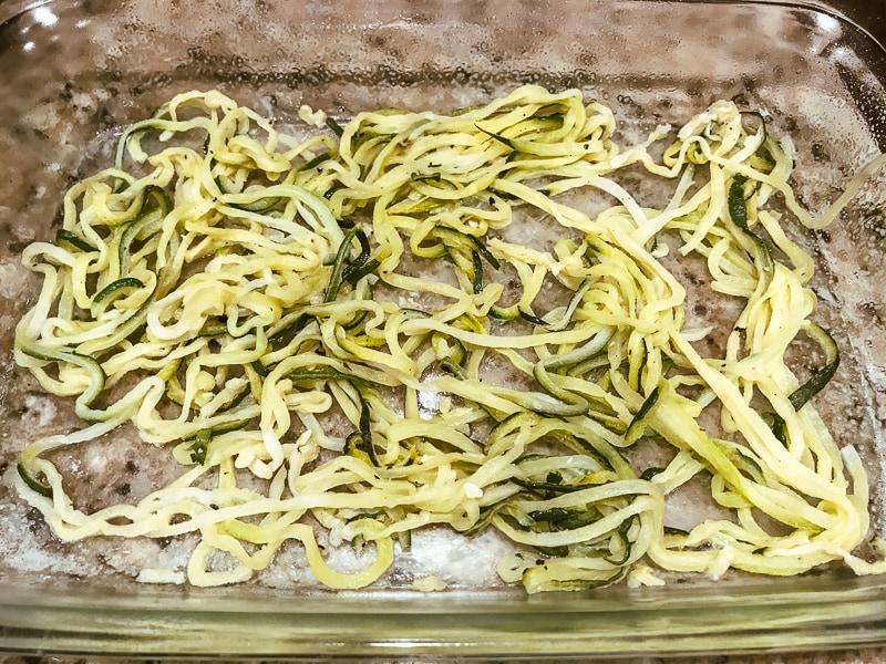 Zucchini noodles in a glass casserole dish.
