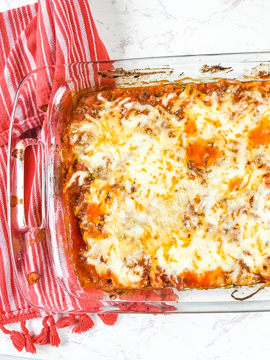 A casserole dish full of zucchini baked ziti next to a red striped towel.