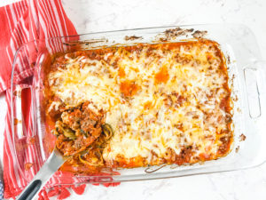 A casserole dish with a pasta spoon filed with a scoop of zucchini baked ziti.