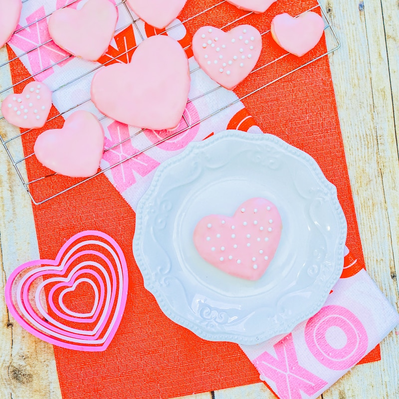 A red place covered in pink heart shaped sugar cookies with pink icing.