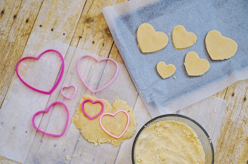 Dough cut into hearts on parchment paper and on cookie sheet.