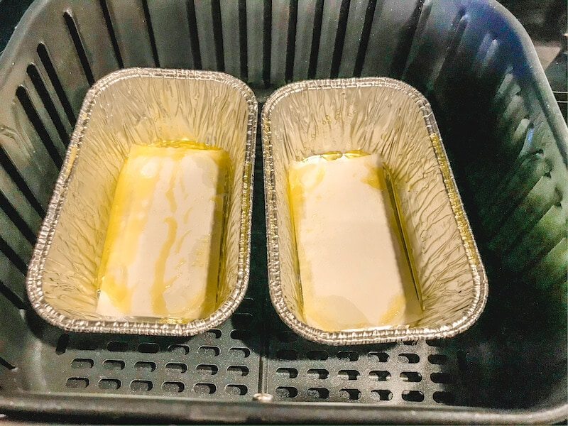 Two foil pans greased with oil inside air fryer basket.
