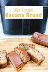 A loaf of banana bread next to slices of banana bread, all in front of black air fryer.