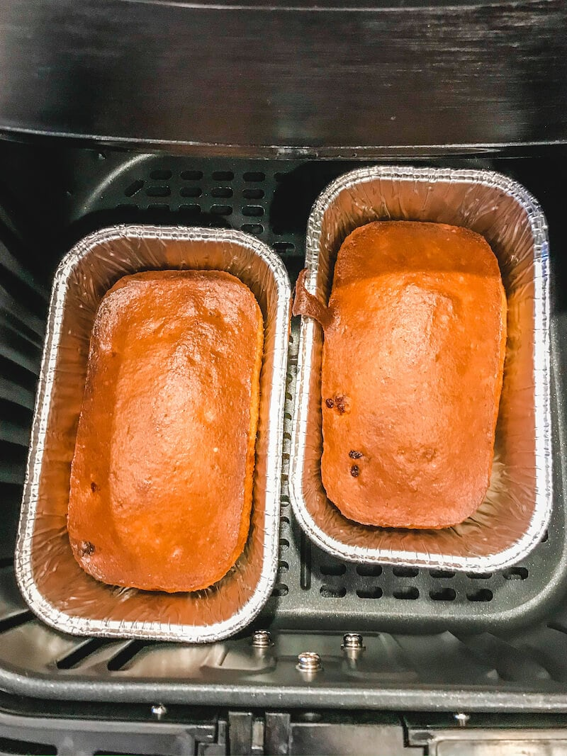 Two cooked loaves of banana bread inside Ari fryer basket.