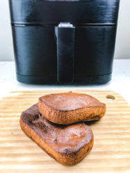 Two loaves of banana bread stacked up on wooden cutting board in front of air fryer