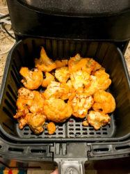 Buffalo cauliflower inside air fryer basket.