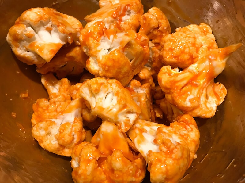 Cauliflower coated in a metal bowl, coated in buffalo sauce.