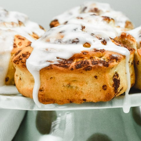 Close up of cinnamon rolls on a cake stand.