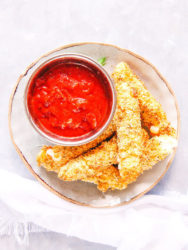Overhead picture of mozzarella sticks and marinara sauce on a small grey plate.