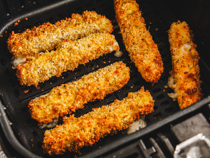 Golden brown mozzarella sticks inside air fryer.