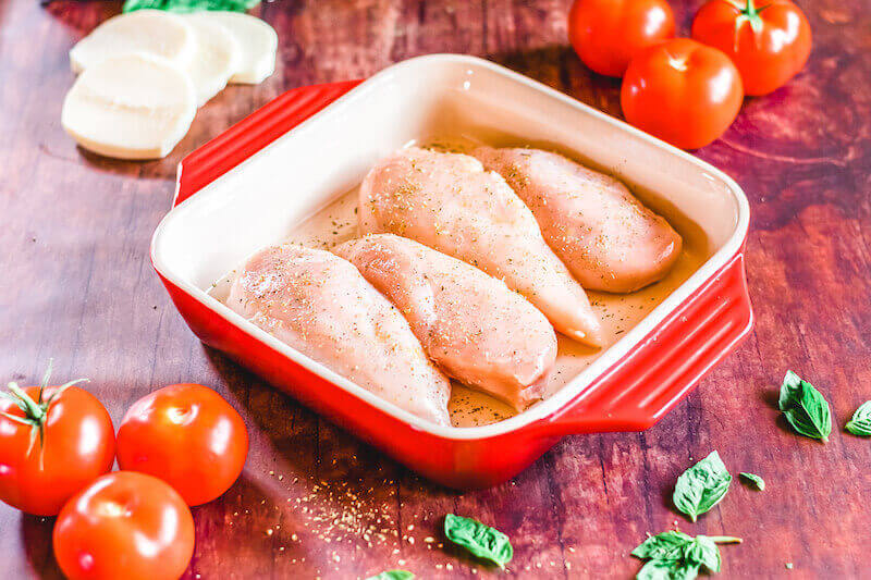 4 chicken breasts inside a red baking dish and coated with olive oil and seasoning.