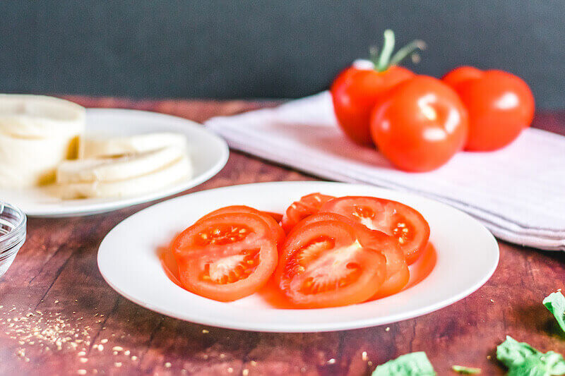 Slices of tomatoes on a white plate with slices of mozzeralla on a white plate behind the plate of tomatoes.