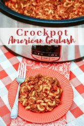 A crockpot with the lid off and filled with meat and pasta behind a red plate of goulash and a fork.