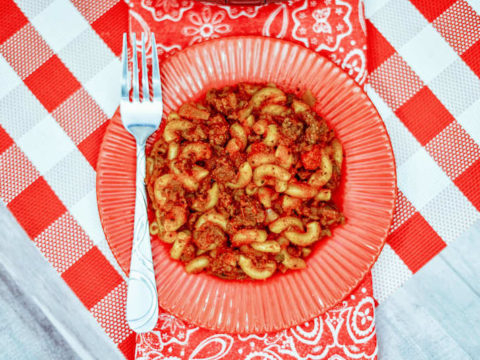 A red plate of goulash on top of a checkered tablecloth.