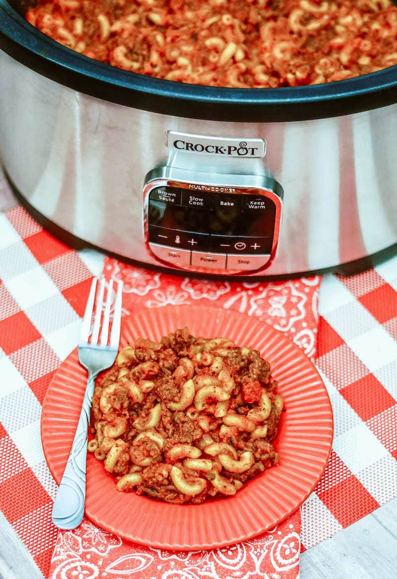 A plate of goulash in front of a crockpot filled with American goulash.