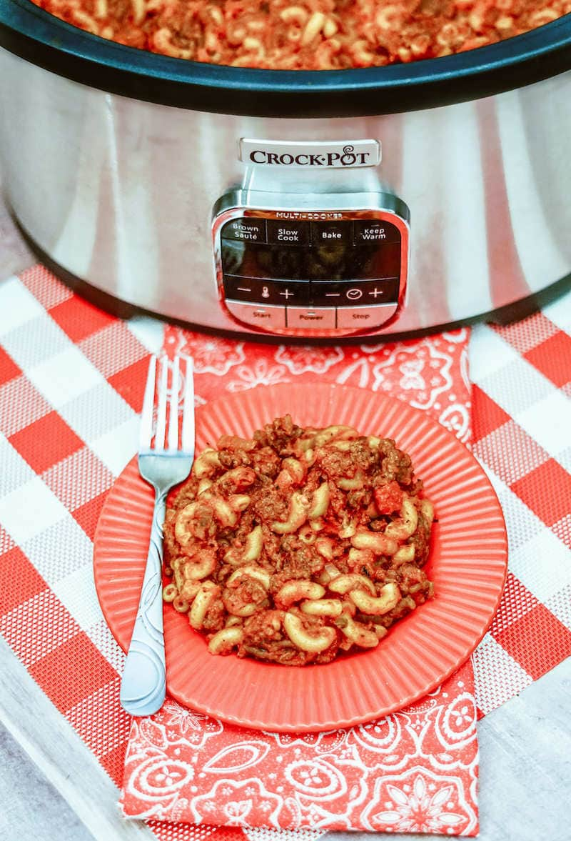 A plate of goulash in front of a sliver crockpot.