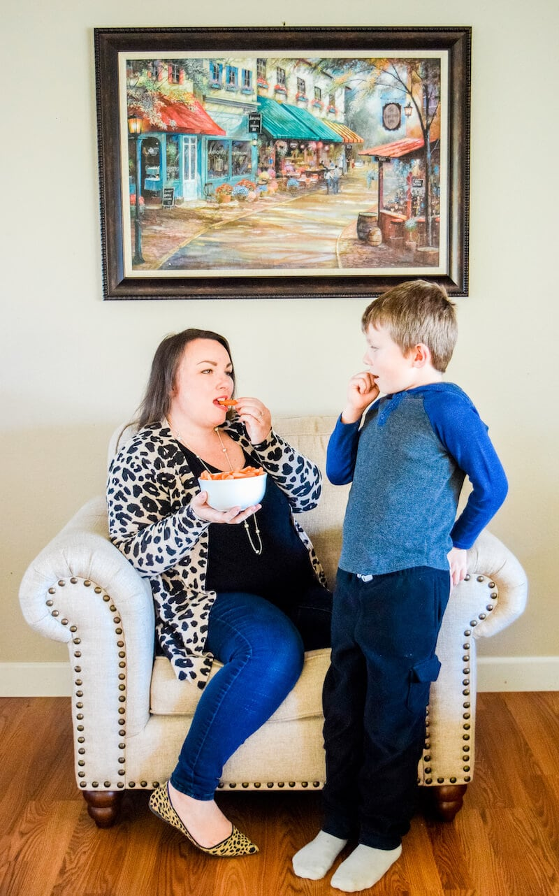 A mom and son looking at each other and eating carrots.