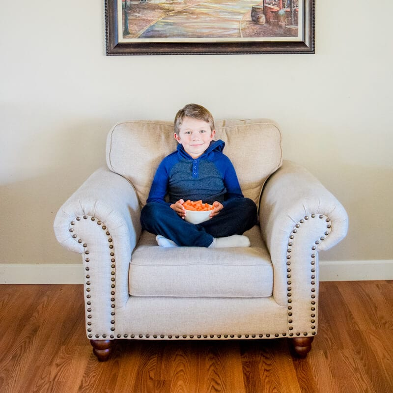 Boy in blue sitting cross legged on a white plus chair with a bowl of baby carrots in his hands.