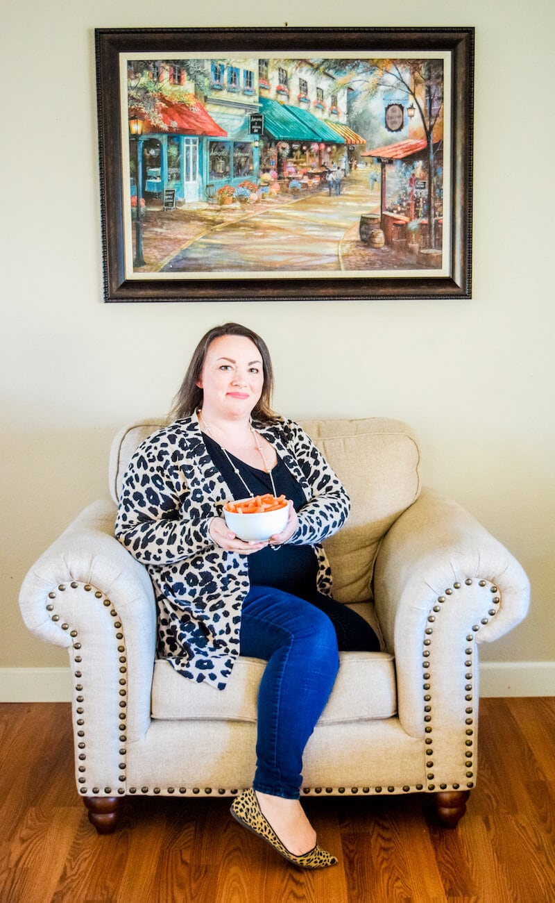 A woman lounging on a beige sitting chair holding a white bowl filled with baby carrots.