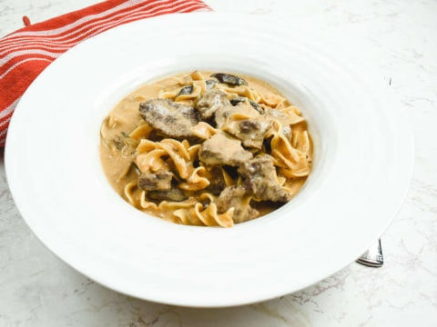 Side angle view of beef stroganoff in a wide rimmed bowl next to a red striped dish towel.