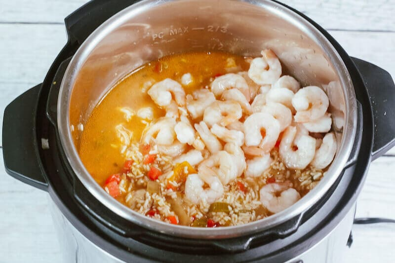 Instant pot filled with cooked jambalaya and shrimp on top.