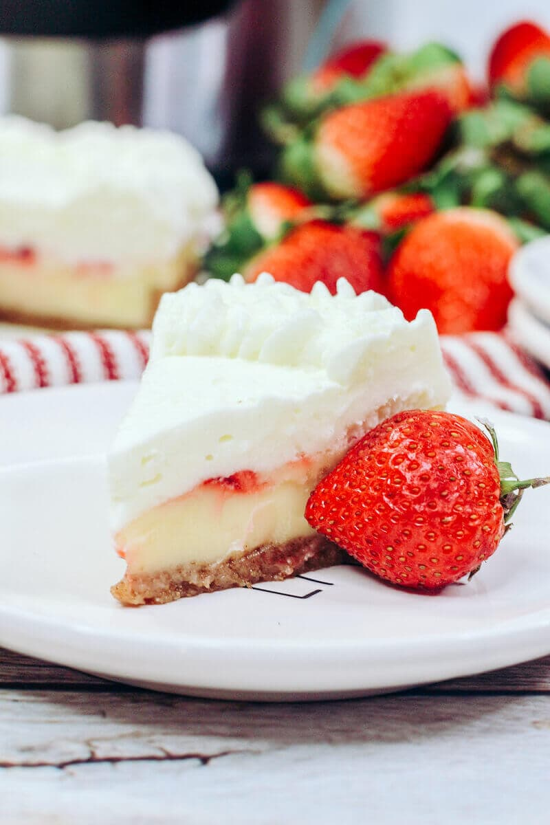 A slice of strawberry cheesecake on a white plate with a strawberry next to it.