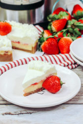 Overhead shot of a slice of strawberry cheesecake next to the whole cheesecake.