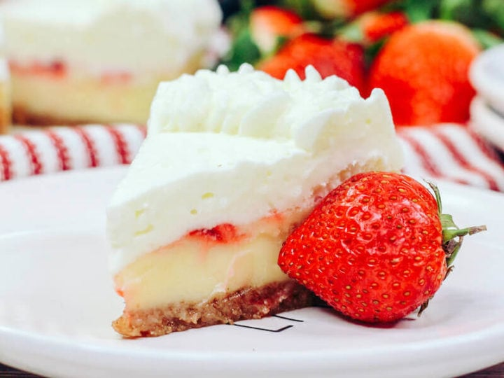 A pile of strawberries behind a slice of strawberry cheesecake.