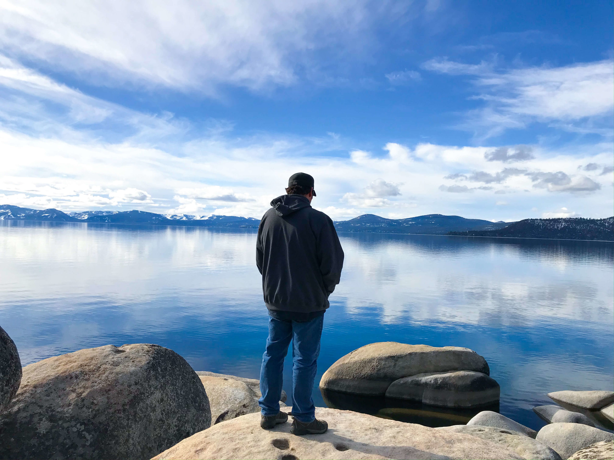 A man standing on a rock in front of Lake Tahoe.