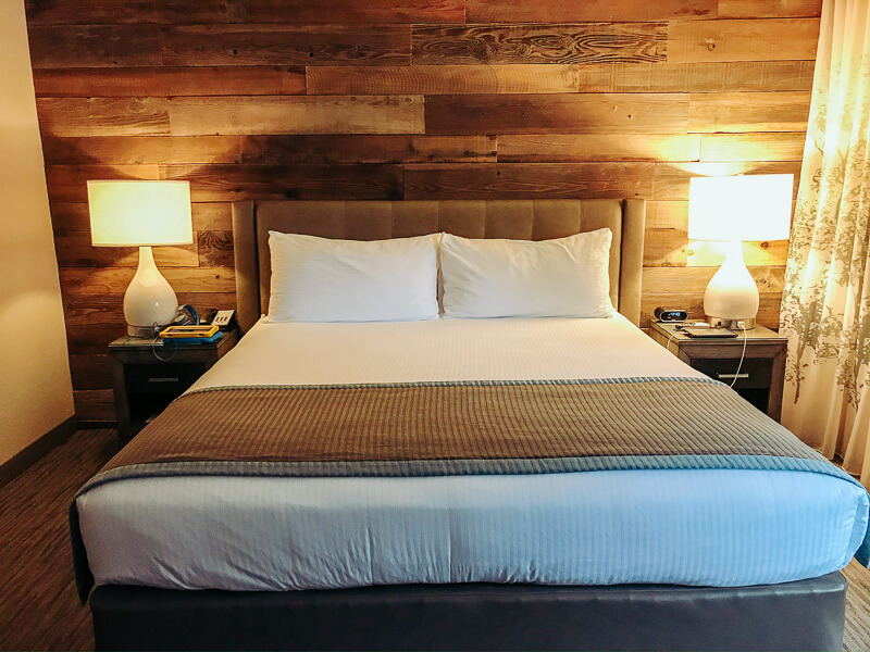 A king sized bed with a modern wood paneling on the wall behind it.